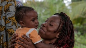 Back in her parents' village in the shade of the large mango tree, Pulcherie holds her daughter in her arms. She takes in every detail – from eyelashes to tiny toes.